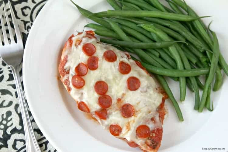 Pizza chicken and green beans on white plate