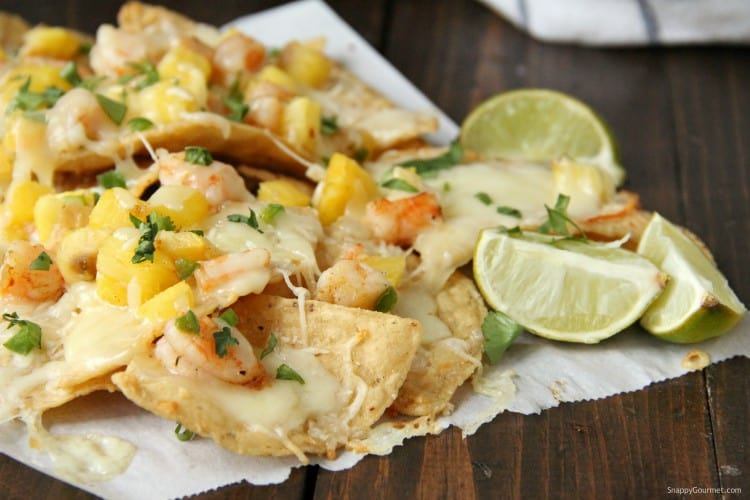 Shrimp Nachos on paper with lime wedges