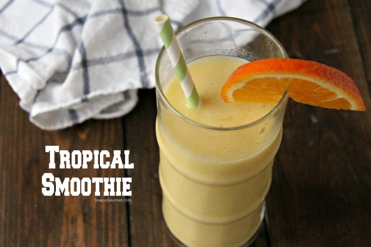 Tropical Smoothie in glass with striped straw and orange slice